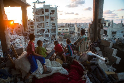 Ann Paq, 'Palestinian family members sit in their home, which was destroyed during Operation Protective Edge (Tsuk Eitan), in al-Tuffah district in Gaza City. Over 18,000 housing units were destroyed or damaged, and 2,000 Palestinians were killed during 50 days. September, 2014', 2014