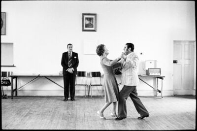 David Goldblatt, 'Dancing-master Ted van Rensburg watches two of his ballroom pupils, swinging to a record of Victor Sylvester and his Orchestra, in the MOTHS' Hall at the old Court House, Boksburg. 1980', 1980