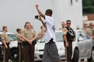Whitney Curtis, 'James Ford, Jr. approaches St. Louis County police to question them as to why they are choosing to block a section of West Florissant Avenue on Sunday, Aug. 17, 2014 in Dellwood, Mo ', 2014