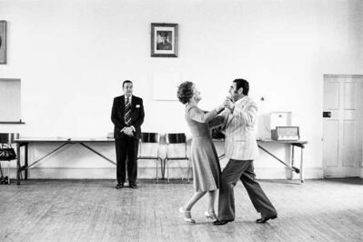 David Goldblatt, 'Dancing-master, Ted van Rensburg, watches two of his ballroom pupils swinging to a recording of Victor Sylvester and his Orchestra, in the MOTHS' Hall at the old Court House', 1980