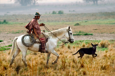 Steve McCurry, 'Cowboy riding his horse with dog running in front', 1988