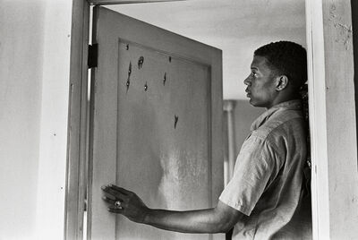 Steve Schapiro, 'Jerome Smith Inspects Bullet Holes in Door', 1963