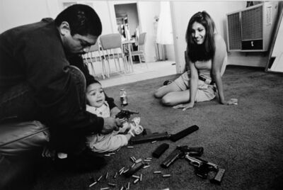 Joseph Rodriguez, 'The morning after a rival gang tried to shoot Chivo for the fourth time, Chivo teaches his daughter how to hold a .32-caliber pistol. Her mother looks on.', 1993