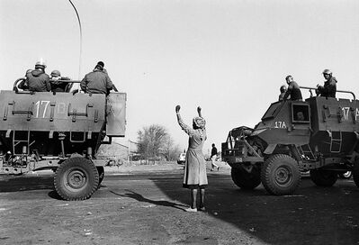 """Paul Weinberg, 'A lone woman protests as the soldiers occupying her township roll by in large military vehicles called, """"hippos"""", Soweto, 1985', 1985"""