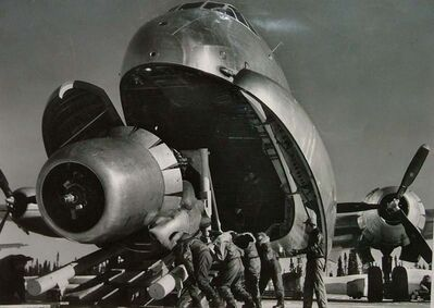 Margaret Bourke-White, 'Crewmen Unloading Huge B-50 Bomber Plane Engine Used as a Spare from the Belly of a C-124 Cargo Plane upon Arrival at Strategic Air Command's Base, Greenland, TX', 1951
