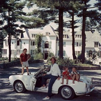 Slim Aarons, 'Mrs. Henry Cabot with her children sitting on a car in the driveway of their home, 'Rollingstones', Manchester, New Hampshire, c. 1960', 1960