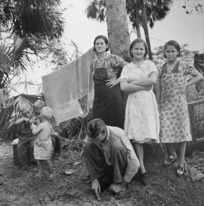 """Marion Post Wolcott, 'Migrant family from Missouri camping out in cane brush. One woman said, """"We ain't never lived like hogs before but we sure does now."""" Canal Point, Florida', 1939"""