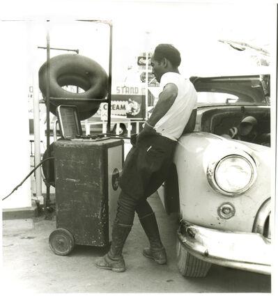 Dorothea Lange, 'Man Working on his Tires, Oakland', 1952