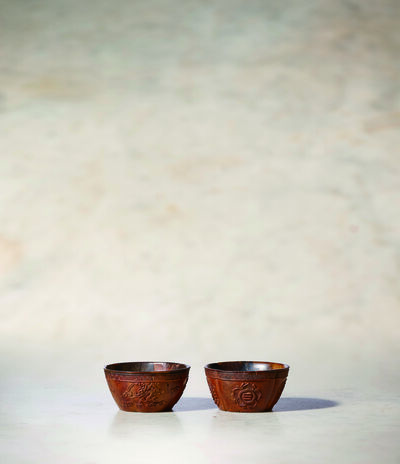 Unknown Chinese, 'A Pair of Coco De Mer Wine Cups of Quatrefoil Form 清乾隆 海椰殼雕菊蓮四葉形酒杯一對	', China: Qianlong (1736-95)