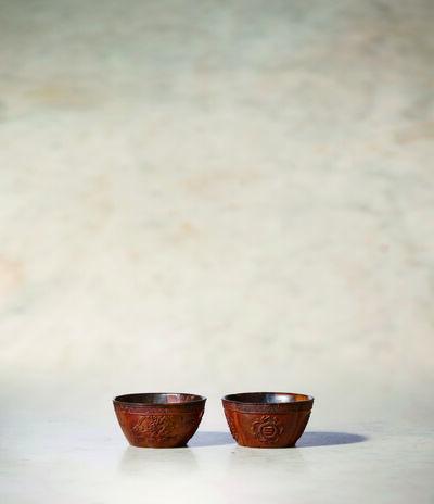 Unknown Artist, 'A Pair of Coco De Mer Wine Cups of Quatrefoil Form 清乾隆 海椰殼雕菊蓮四葉形酒杯一對', China: Qianlong (1736-95)