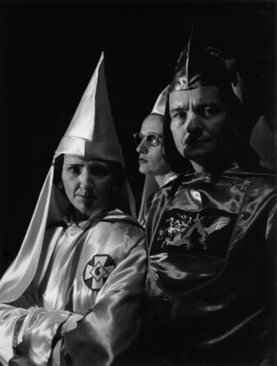 Charles Moore, 'Grand Dragon Jones attends a Klan rally. A Confederate flag is embroidered on his sleeve. The cross on the woman's robe represents the crucifixition; the mark in the center, a drop of Christ's blood', 1965