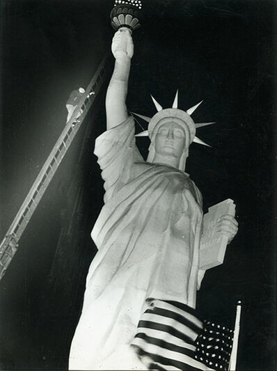 Weegee, 'Man climbs 85-foot ladder to secure torch on the plastic Statue of Liberty erected at Times Square for the Sixth War Loan Drive, New York', 1944