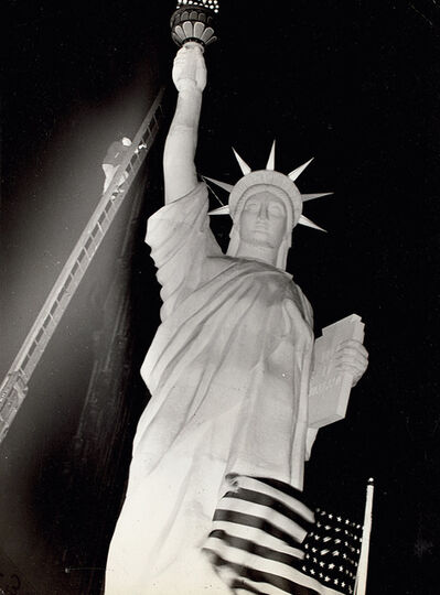 Weegee, 'Man climbs 85-foot ladder to secure torch on the plastic Statue of Liberty erected at Times Square for the Sixth War Loan Drive, New York, November 30', 1944