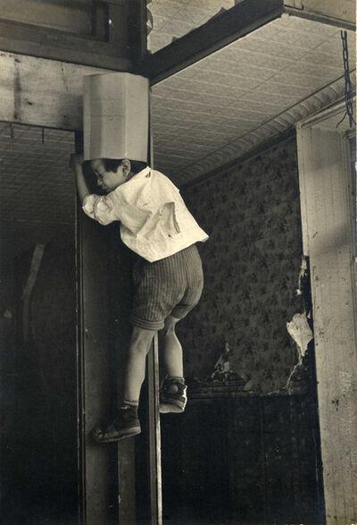 Helen Levitt, 'N.Y.C. (boy in box hat climbing up doorframe)', 1938