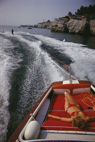 Slim Aarons, 'Leisure in Antibes, 1969: A woman sunbathes on a motorboat as it tows a waterskier in the bay off the Eden-Roc', 1969