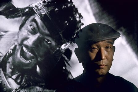 Brian Brake, 'Film director Akira Kurosawa standing before an image of his principal star, Toshiro Mifune, Tokyo, Japan', 1963