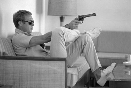 John Dominis, 'Steve McQueen aims a pistol in his living room, California', 1963