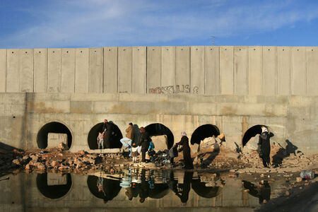 Alex Levac, 'Palestinian Families walk by the West Bank Separation Wall in Dahiyat al Barid, a Palestinian neighborhood in northern Jerusalem. In several locations, the Wall severs predominantly-Palestinian residential areas, leaving parts of it outside the wall, and parts of it in it. December, 2007', 2007