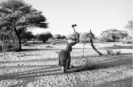 Margaret Courtney-Clarke, 'Maria Bessa !Gubi cops wood behind her shack at SAA TA KO, a once thriving rest camp run by local !Xoon Bushmen. Corridor 17 Kalahari, Namibia', 2019