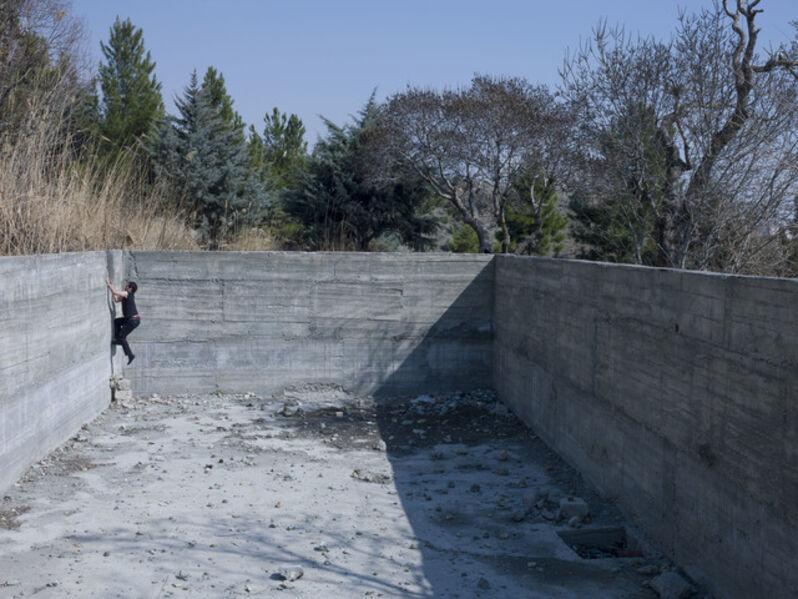 "Newsha Tavakolian, 'Mahud climbing the wall of the abandoned swimming pool.  Teheran, Iran.  ""Blank Pages of an Iranian Photo Album""', 2014"