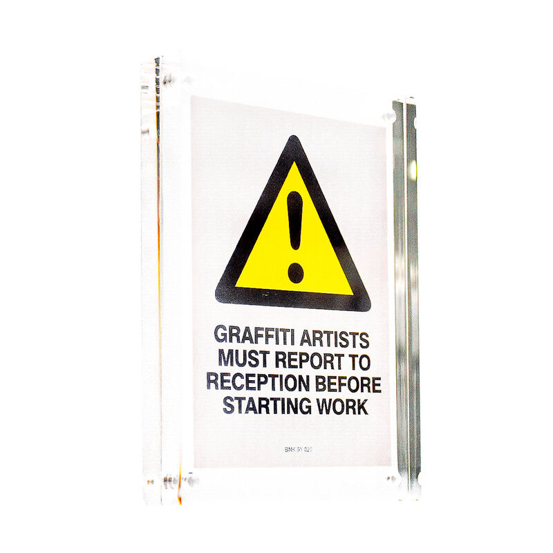 Banksy, 'GRAFFITI ARTISTS MUST REPORT TO RECEPTION STICKER (Framed)', ca. 2004, Ephemera or Merchandise, Vinyl sticker printed in colors on Starliner paper. Framed in new clear block acrylic frame., Silverback Gallery
