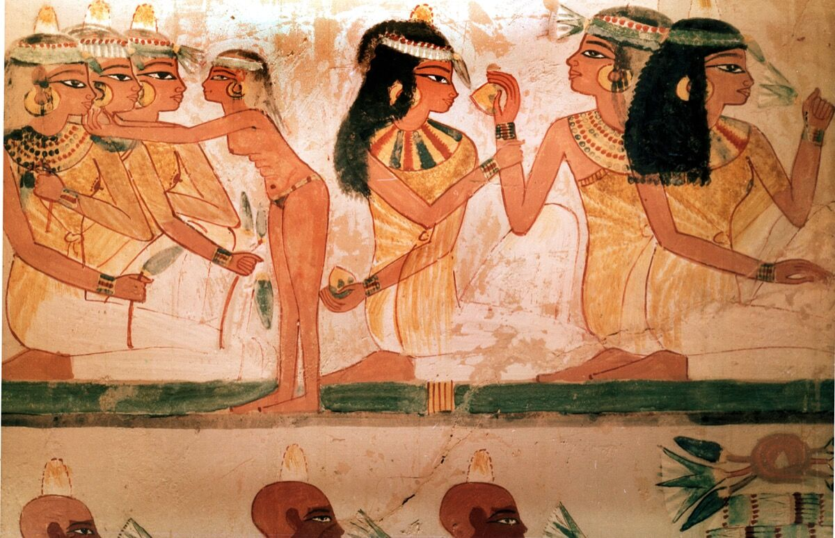 A detail of a painting from the tomb of Nakht depicting three ladies at a feast. They wear perfumed cones in their hair and elaborate necklaces. Egypt, 18th dynasty, ca. 1421–1413 B.C.E. Tomb no. 52, West Thebes. (Photo by Werner Forman/Universal Images Group/Getty Images).