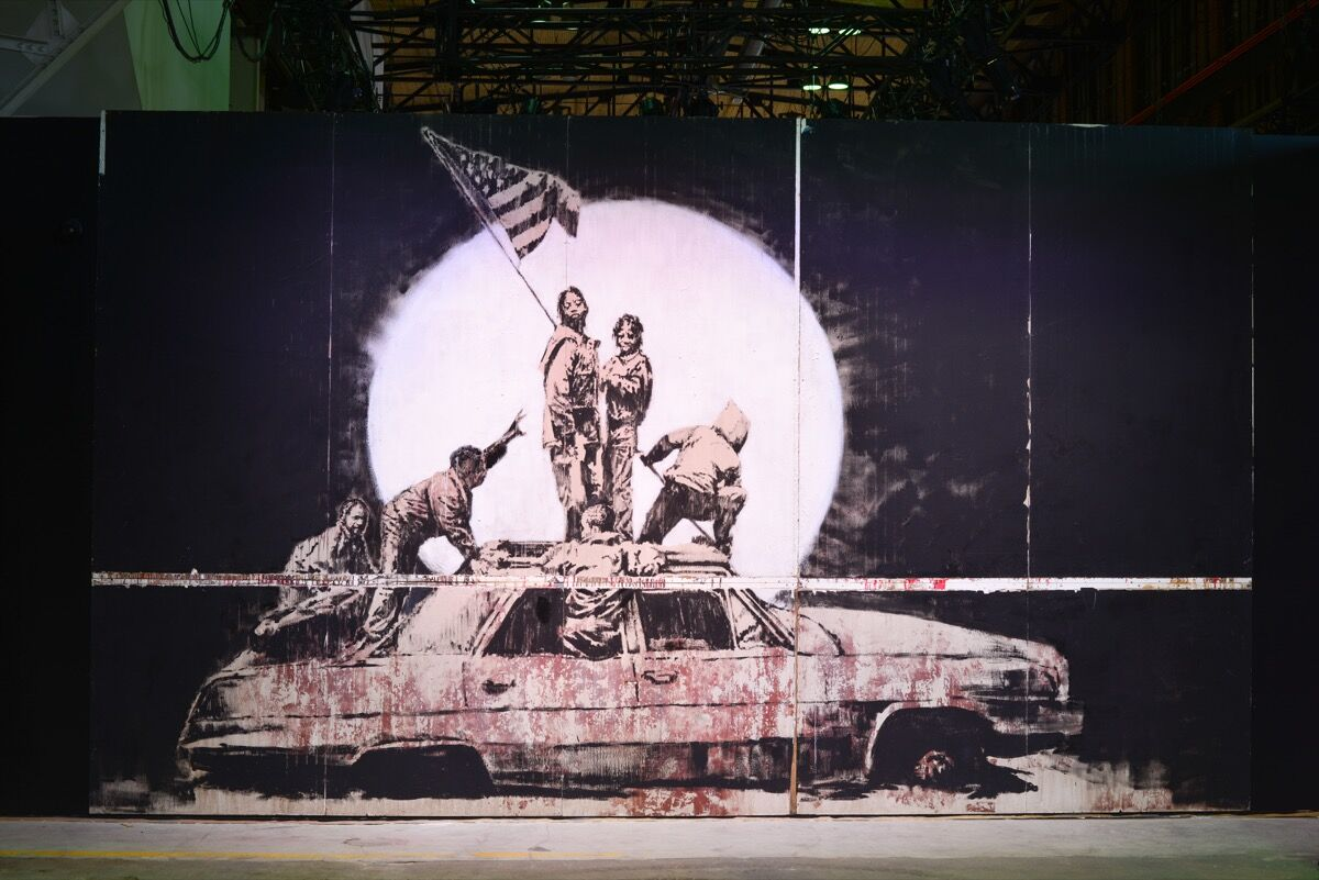 """Installation view of Banksy, Flag Wall, in """"The Art of Banksy."""" Courtesy of """"The Art of Banksy."""""""