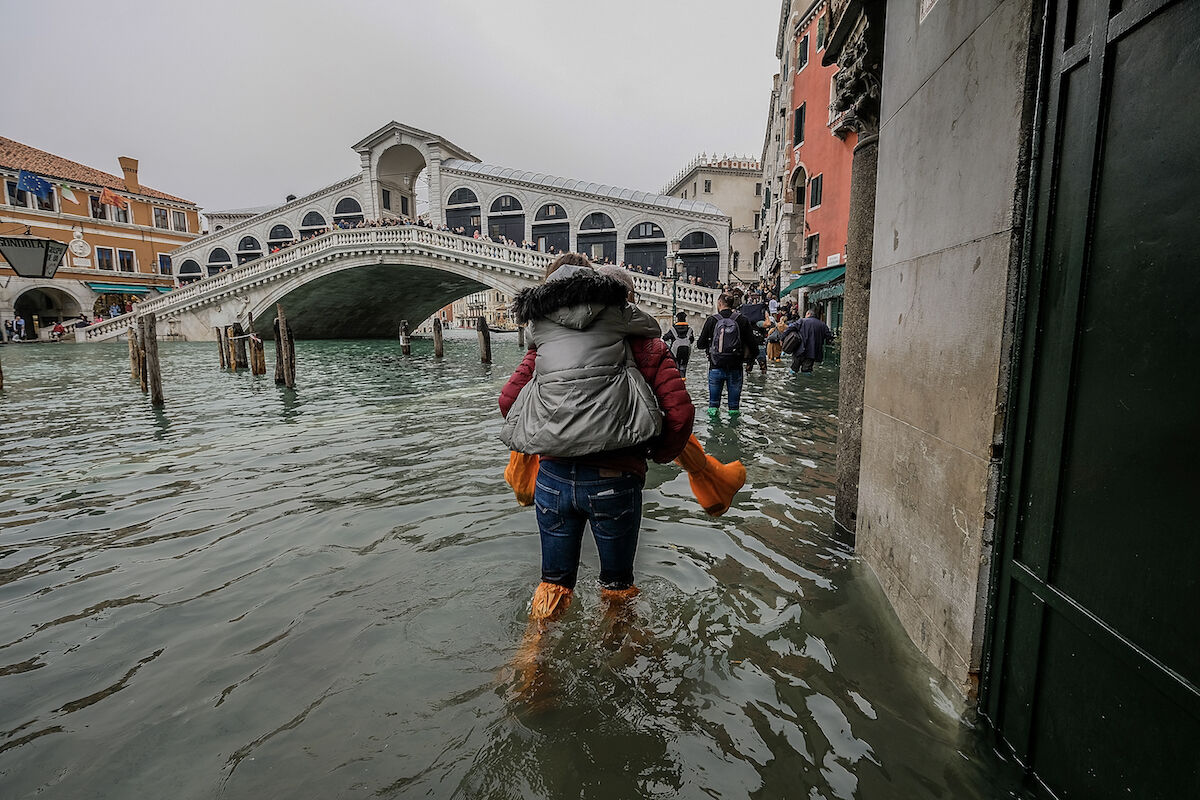 A tourist carries his partner on his shoulders in on October 29, 2018 in Venice, Italy. Photo by Stefano Mazzola/Awakening/Getty Images.