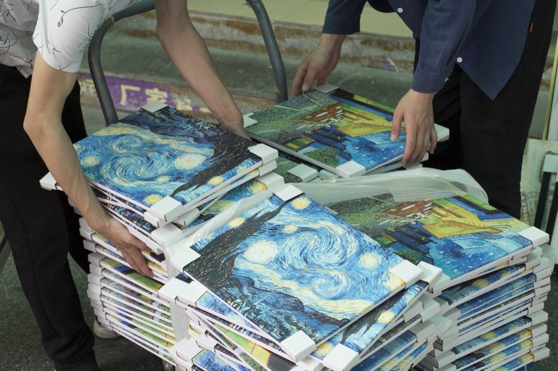 Dozens of copies of Vincent van Gogh, The Starry Night, 1889 are delivered to a gallery on the eastern edge of Dafen. Photo by Adam Kuehl for Artsy.