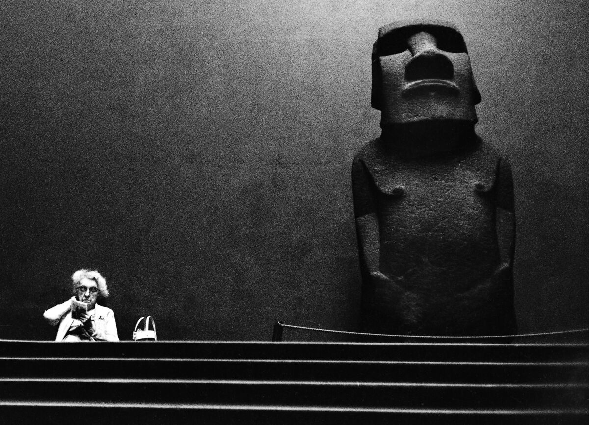 An elderly woman sits reading by a Moai sculpture from Easter Island on display at the British Museum, London, 1967. Photo by Romano Cagnoni/Hulton Archive/Getty Images.