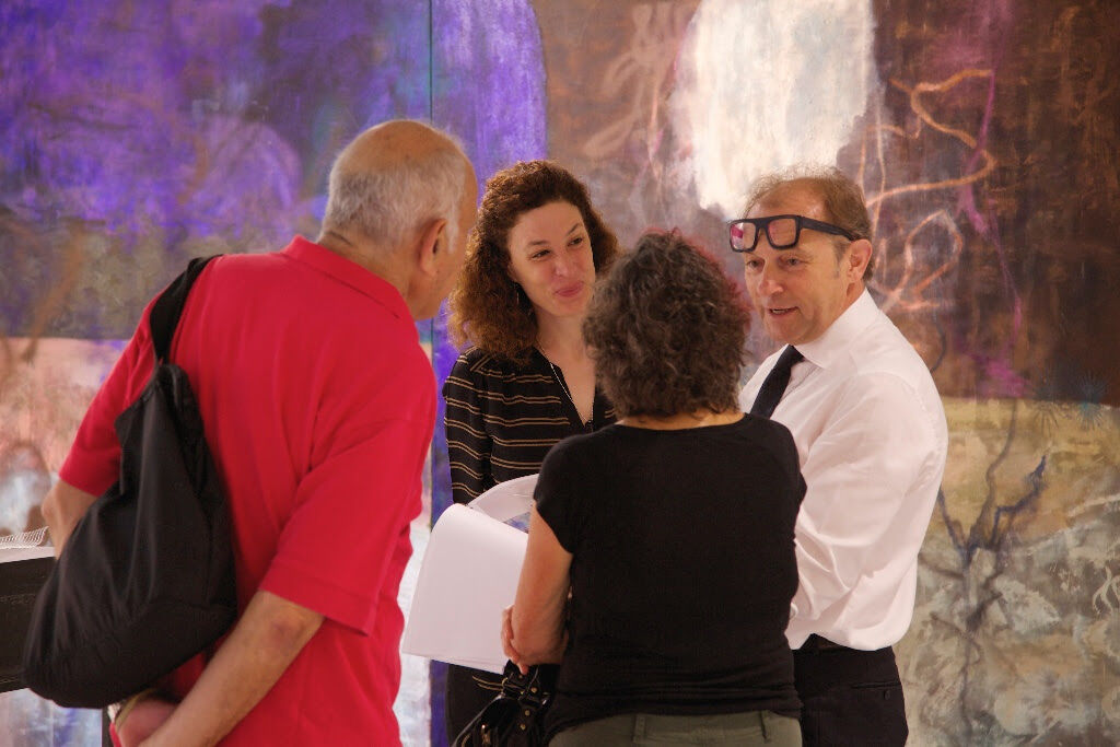 "Josef Zahorian (right) and Silvia Van Espen (center), co-directors of Zahorian & Van Espen (Bratislava/Prague) engage with collectors Susan and Michael Hort around a ""tie-dye"" painting by Viktorie Langer"