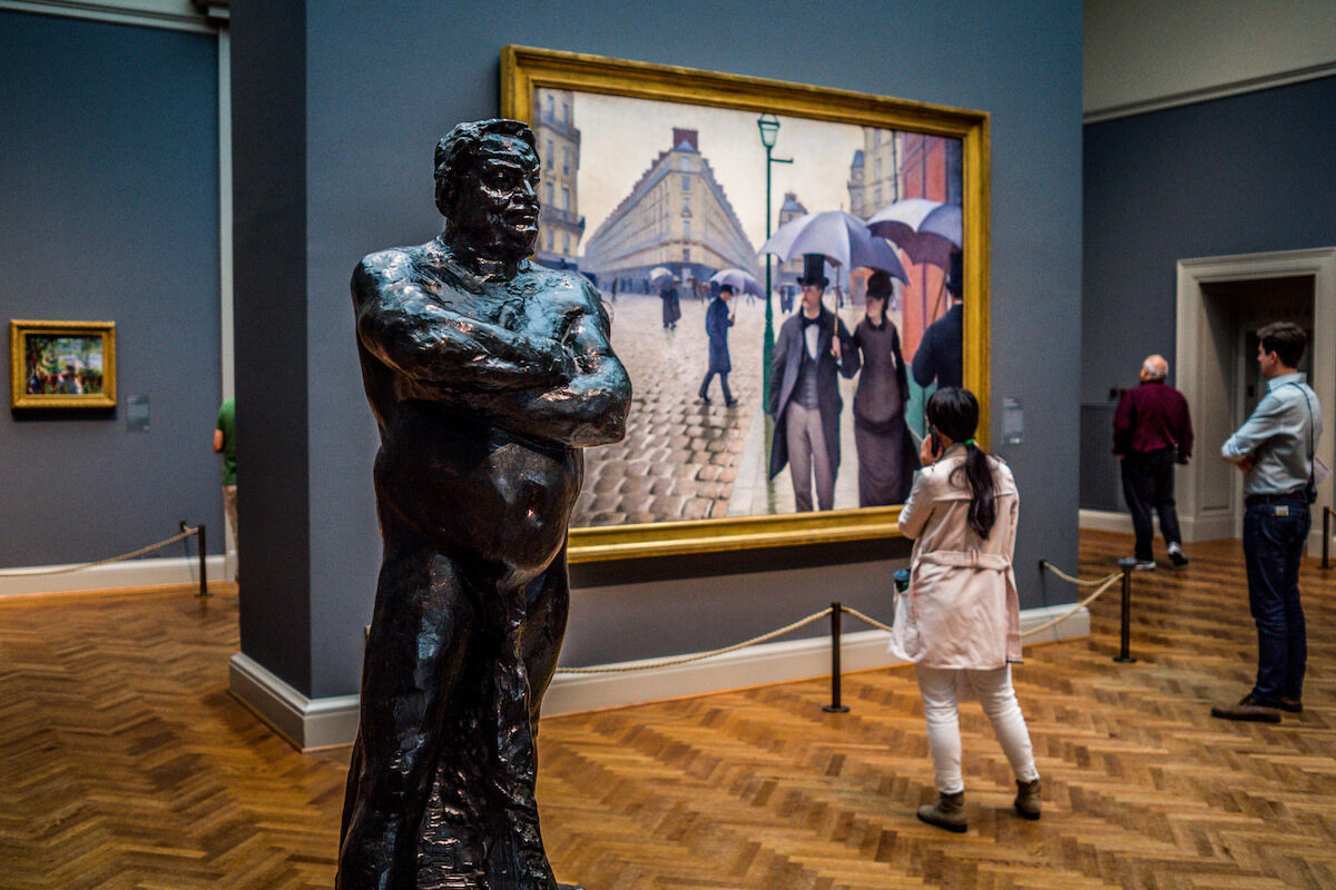 An Auguste Rodin sculpture and Paris Street; Rainy Day (1877) by Gustave Caillebotte at the Art Institute of Chicago. Photo by Phil