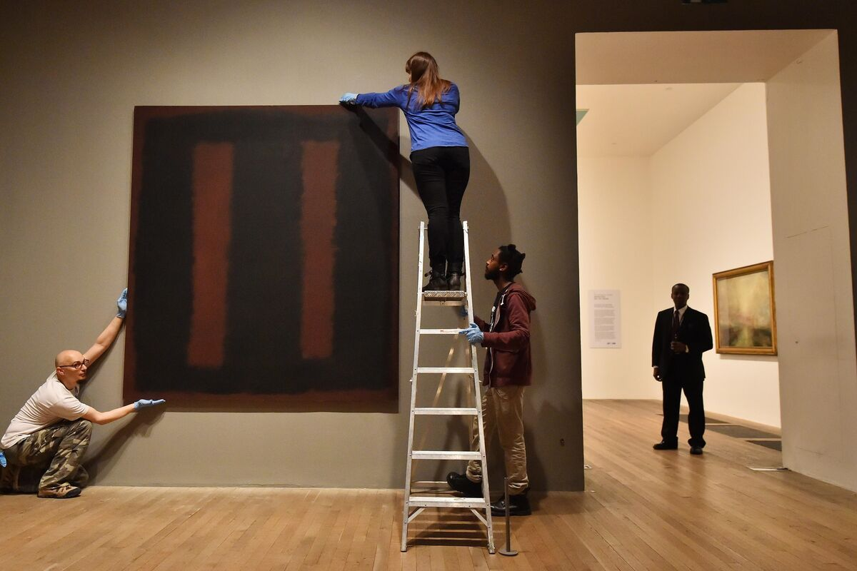 Employees hanging Black on Maroon (1958) at the Tate Modern in London. Photo by Ben Stansall/AFP/Getty Images.