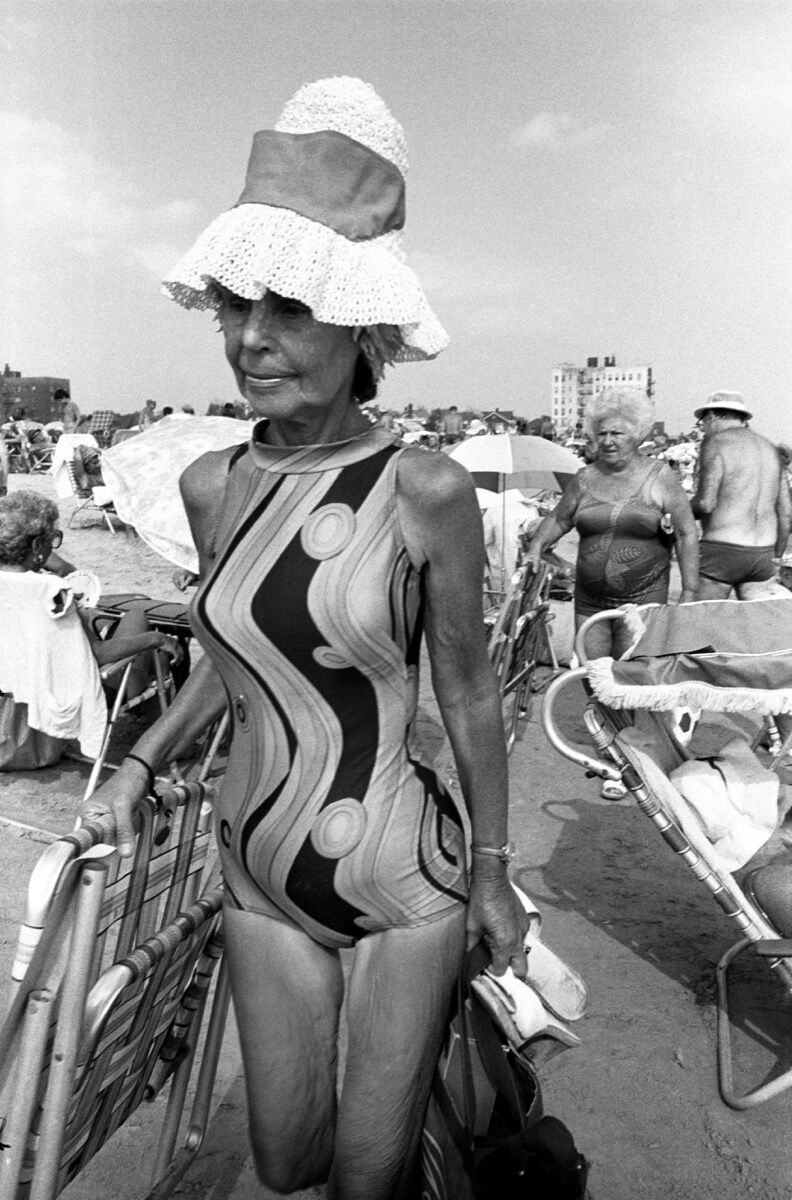 Bruce Gilden, A woman in a bathing suit and hat walks on a crowded beach, Coney Island, New York City, 1982. © Bruce Gilden/Magnum Photos. Courtesy of Magnum Photos.