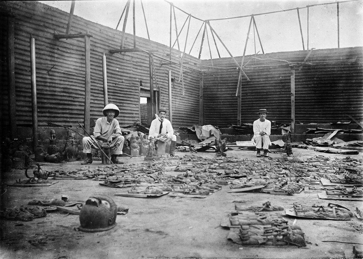 Interior of Oba's compound burnt during the siege of Benin City, with bronze plaques in the foreground and three British soldiers of the Benin Punative Expedition, February 9–18, 1897. Photo by Reginald Granville, via Wikimedia Commons.