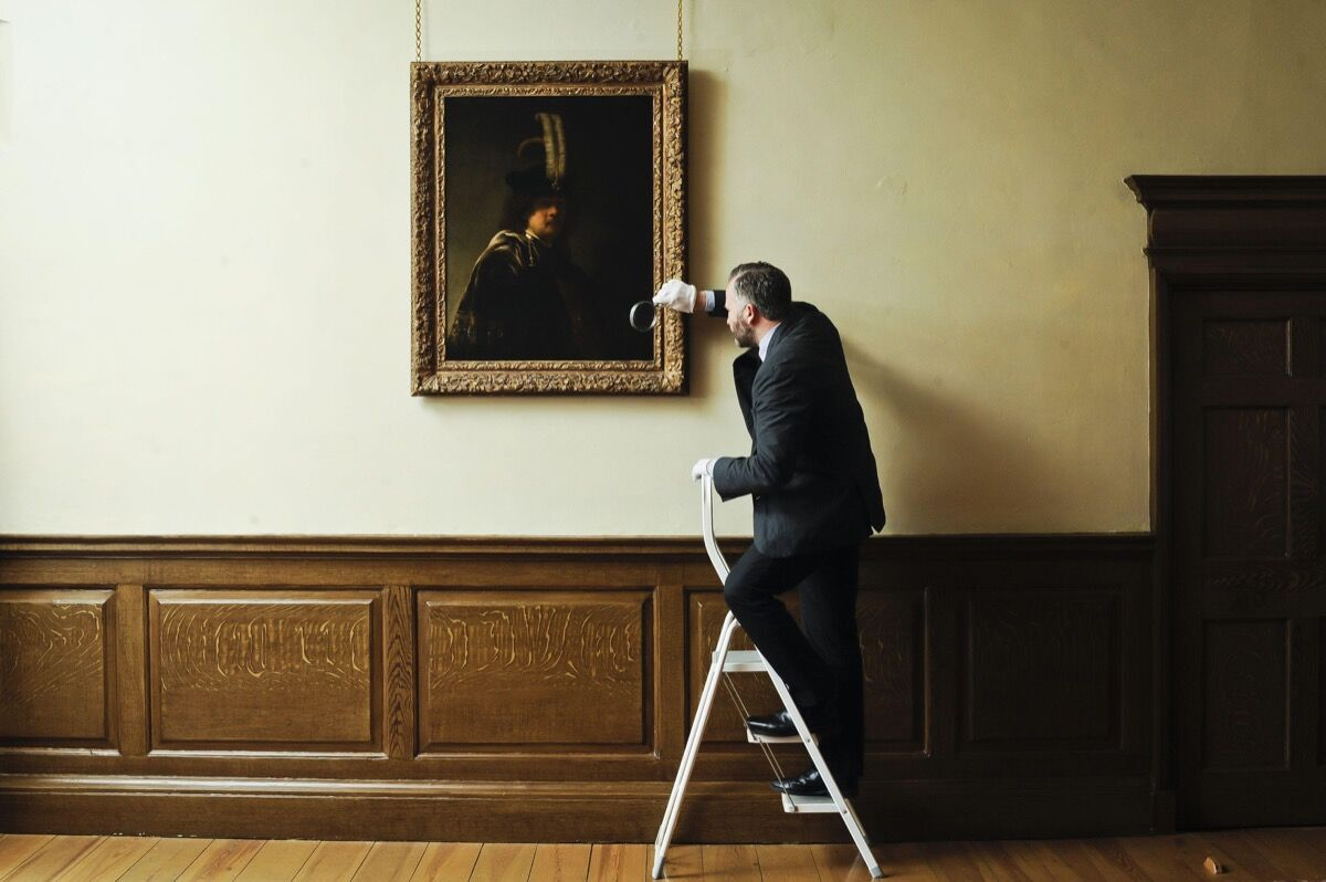 Curator of Pictures and Sculpture at Buckland Abbey David Taylor inspects a confirmed self-portrait of Rembrandt discovered at the Devonshire Abbey. Photo by Ben Birchall/PA Images via Getty Images.