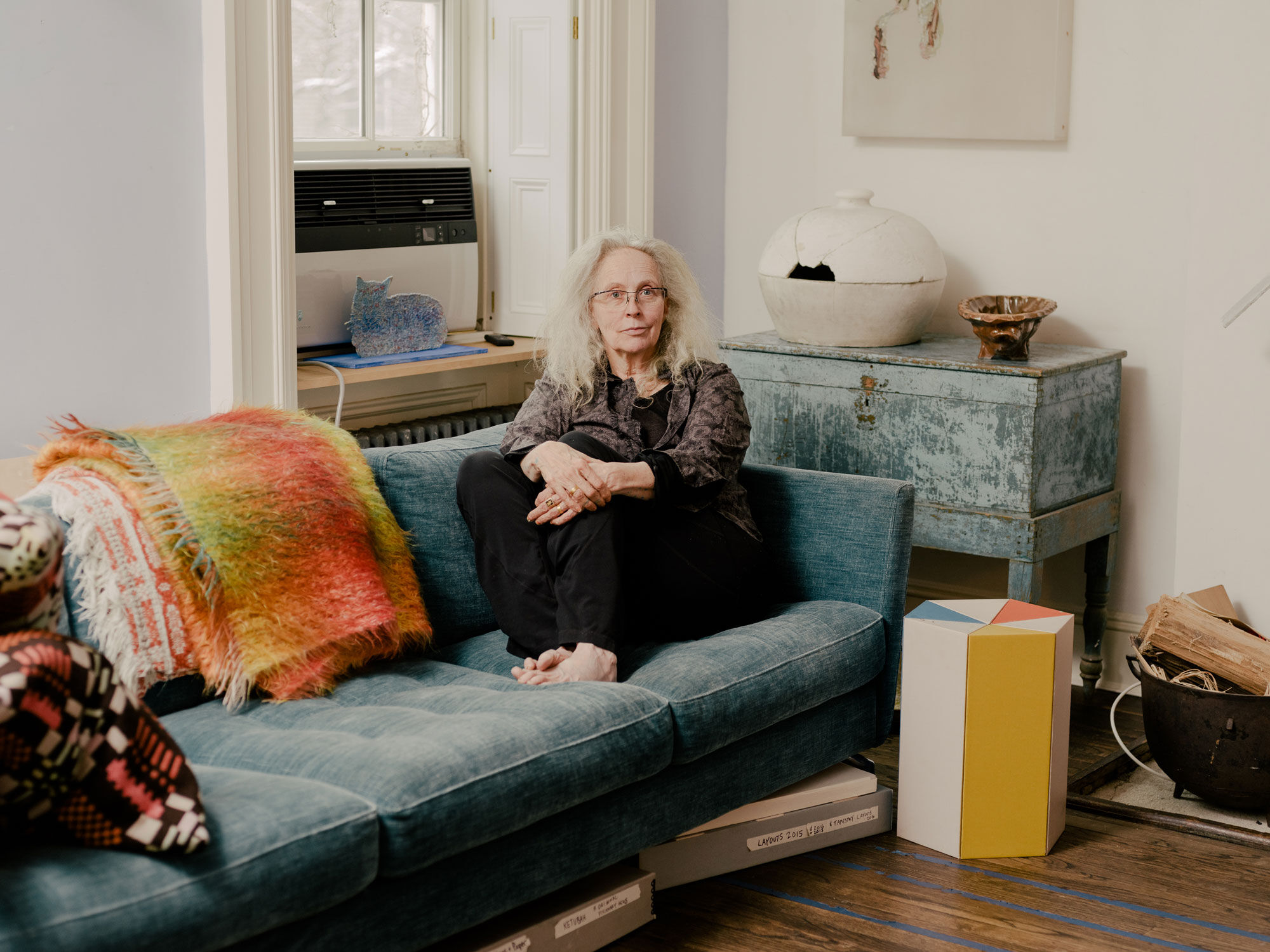 Portrait of Kiki Smith in her New York home and studio. Below the couch, archival boxes store rubbings and templates from past work. Portrait by Daniel Dorsa for Artsy.