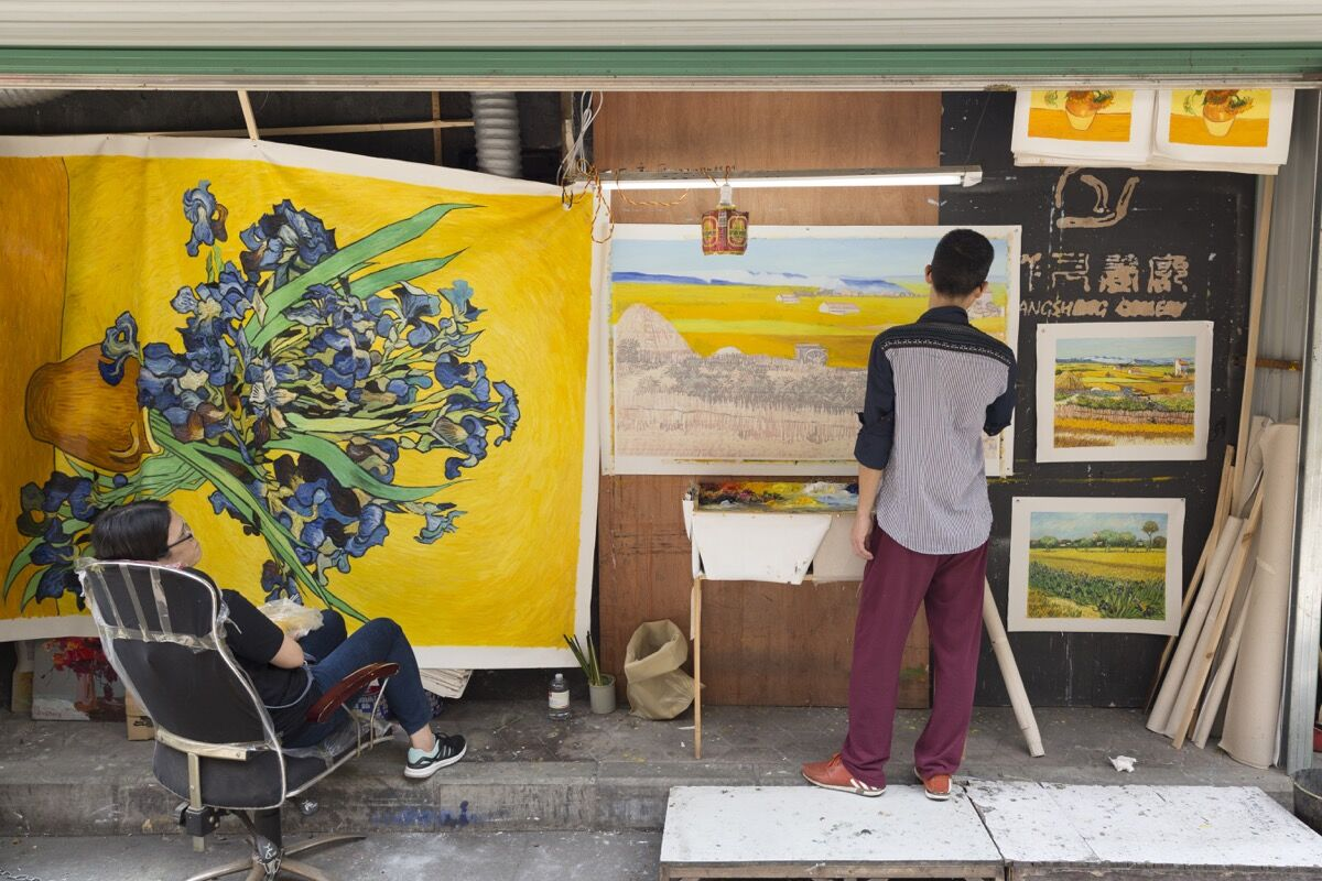 An artist paints in his studio in Dafen. Photo by Adam Kuehl for Artsy.