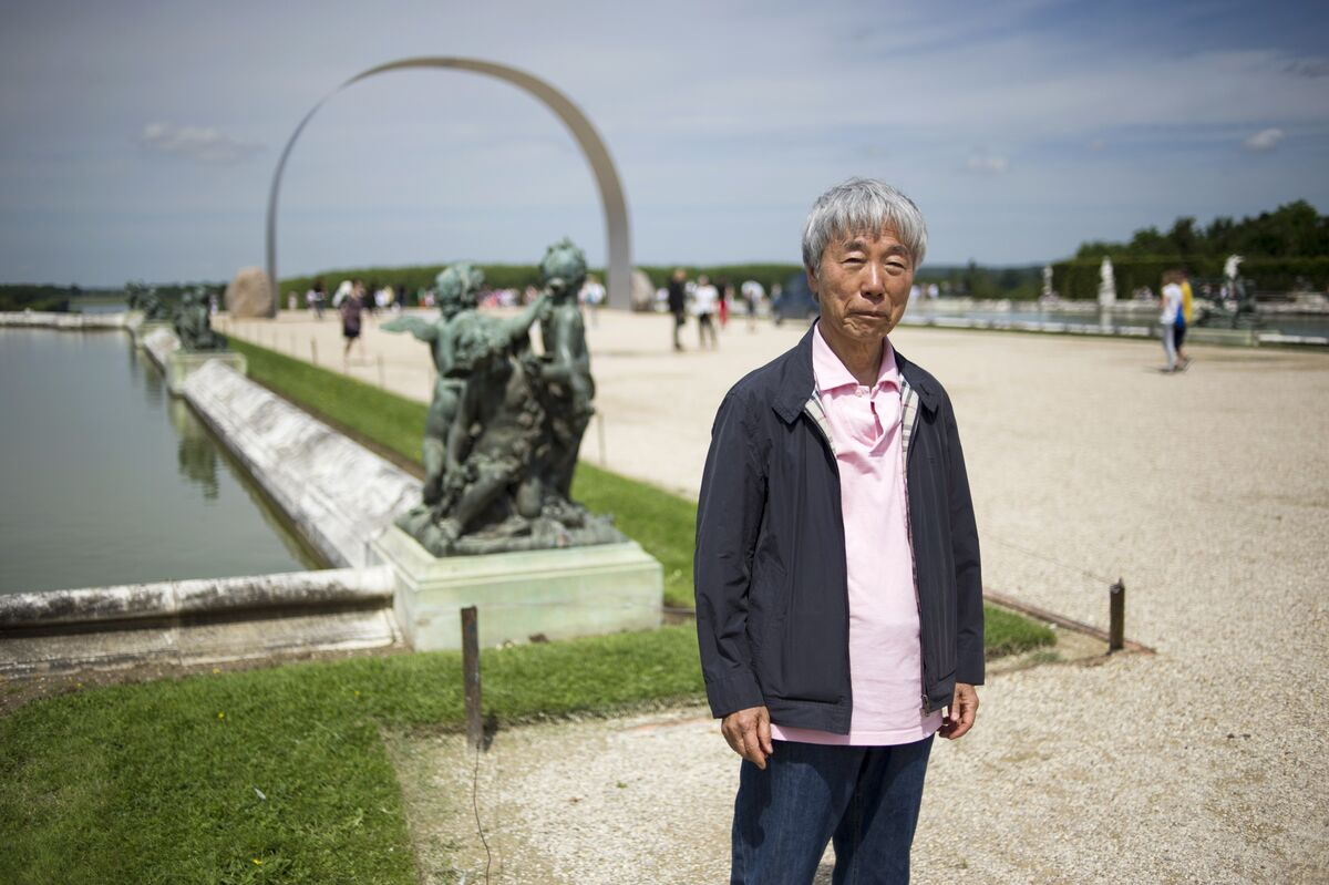 South Korean artist Lee Ufan poses near his artwork L'arche de Versailles (The arch of Versailles), on June 11, 2014, at the Chateau de Versailles. Image courtesy of Fred Dufour and Getty Images.