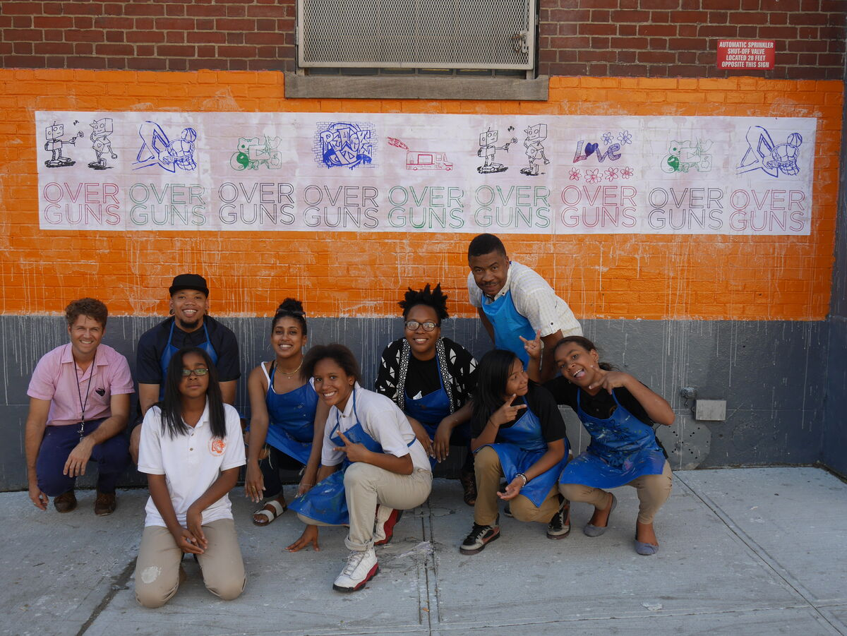 Students at MS 22 in front of a completed anti-gun violence mural. Courtesy of The Bronx Museum of the Arts.