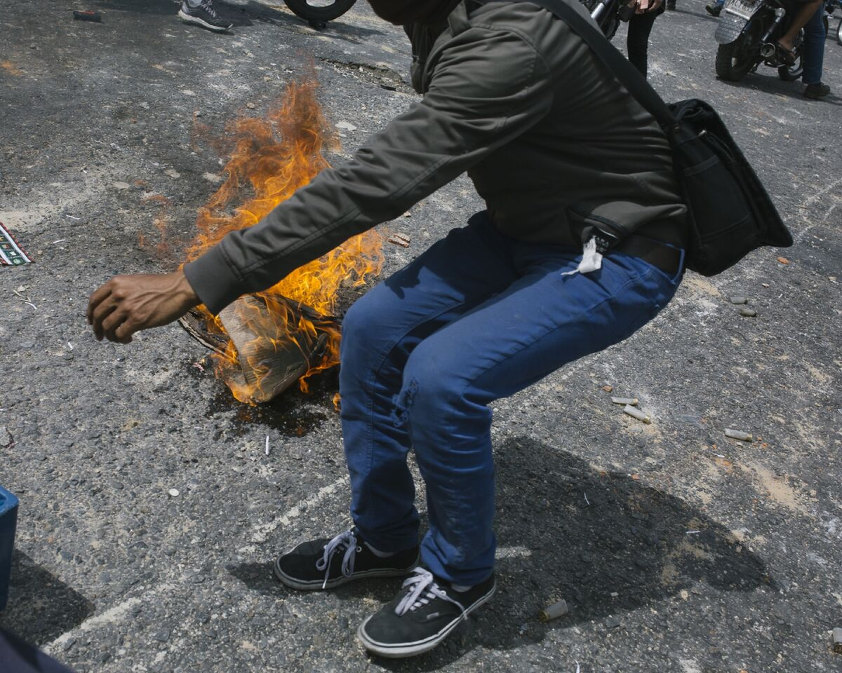 A young man turns to run away from the National Bolivarian Police during a demonstration in support of interim president Juan Guaidó in El Paraíso, Caracas, Venezuela, on January 30, 2019.  Photo by  Andrea Hernández. Courtesy of the artist.