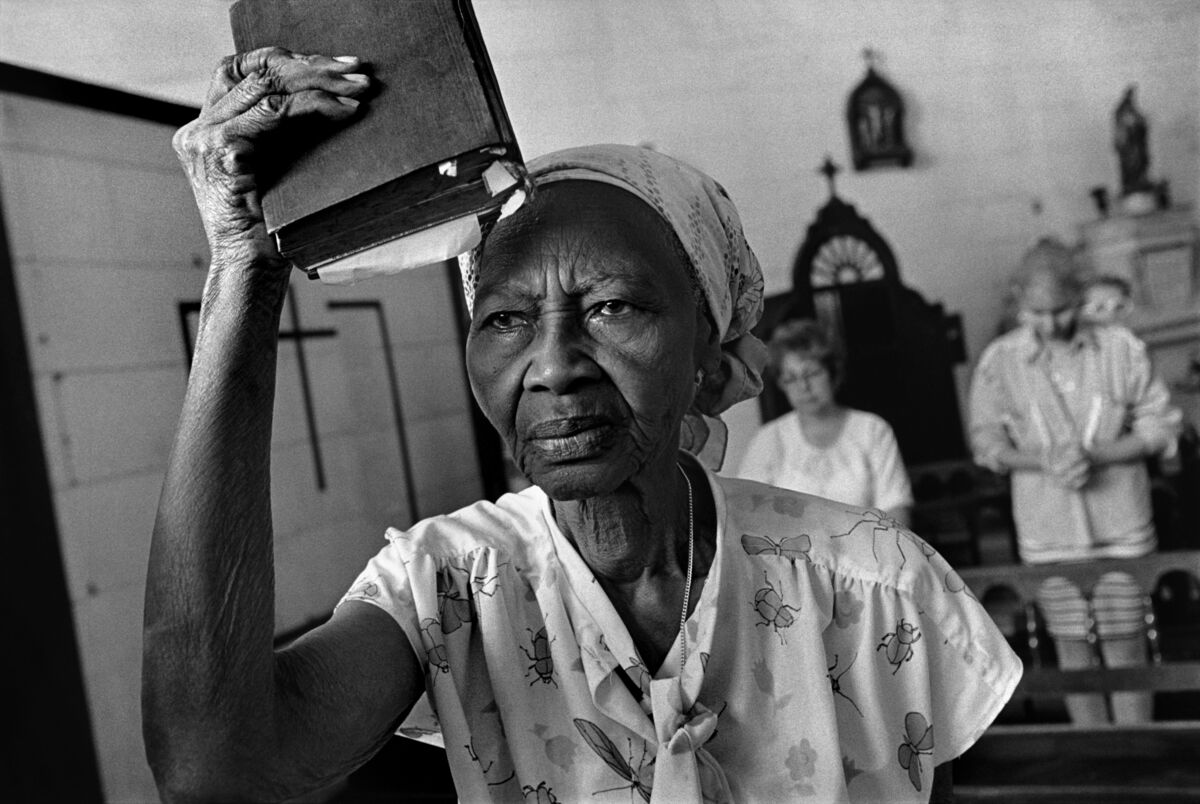 "Abbas, Church of Cristo de Buen Viaje. A woman listening to a sermon raises her Bible as a flag, before going to visit homes to take in ""the Lord's words."" Havana, Cuba, 1997. © Abbas / Magnum Photos, courtesy of Arthur Ross Gallery, University of Pennsylvania."