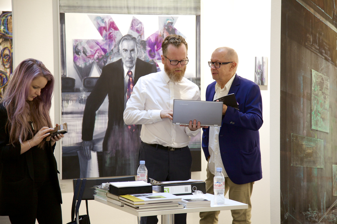Zavier Ellis (center, owner of Charlie Smith London) confers with a collector as gallery manager Rosanna Dean follows up with correspondence. A new Tom Butler painting, part of the gallery's 'Interiority' curated booth, looks on; Courtesy VOLTA13