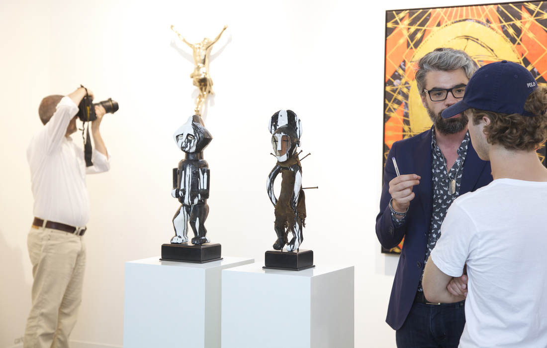 Francesco Giaveri (near right, of ADN Galería, Barcelona) discusses works by Carlos Aires and Kendell Geers with a collector; Courtesy VOLTA13