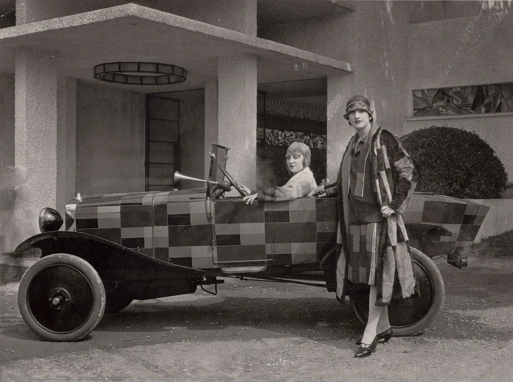 Two models wearing fur coats designed by Sonia Delaunay and manufactured by Heim, with the car belonging to the journalist Kaplan and painted after one of Sonia Delaunay's fabrics, in front of the Pavillon du Tourisme designed by Mallet-Stevens, International Exposition of Modern Industrial and Decorative Arts, Paris 1925. 