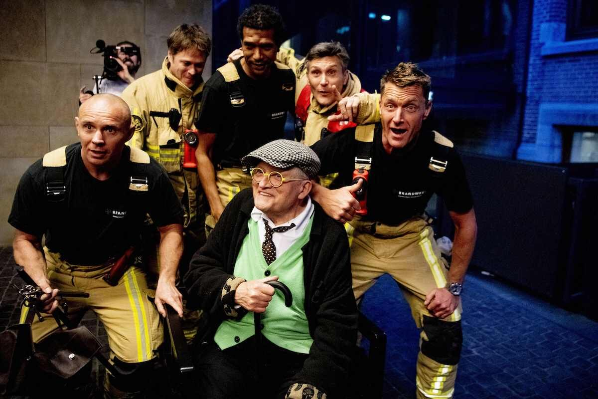 British artist David Hockney poses with his firemen after being freed from an elevator at an Amsterdam hotel on February 27, 2019. Photo by Robin Utrecht/AFP/Getty Images.