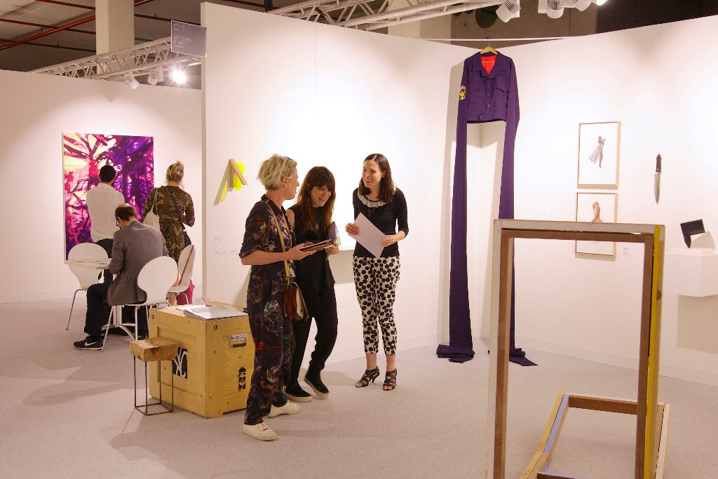 Left: Galleri Flach (Stockholm), presenting a solo project by Pauliina Pietilä; center-right: Reyes Martinez (center, owner of Set Espai d'Art (Valencia), and colleague Kasia Nagórska (right) engage with a collector around works by Ana H. del Amo and Sean Mackaoui