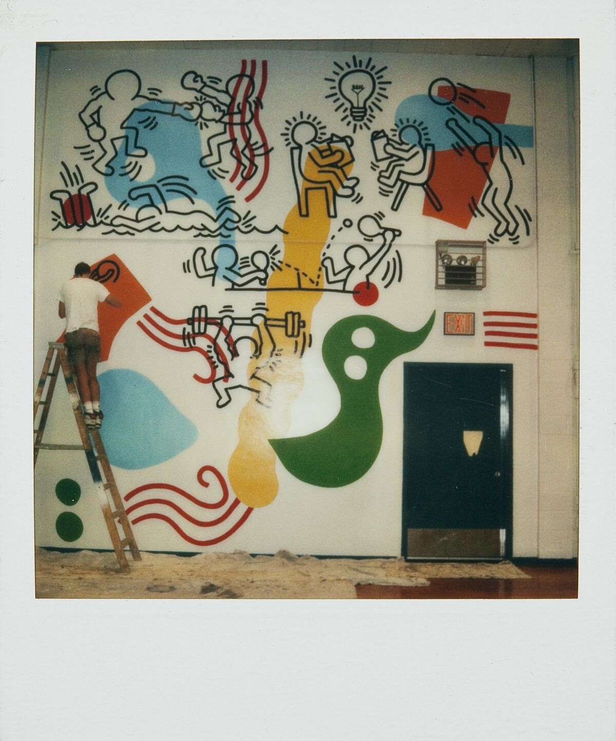 Polaroid of Keith Haring working on the Boy's Club Mural, Pitt Street, New York City, 1987. © Keith Haring Foundation. Courtesy of The Keith Haring Foundation Archives.