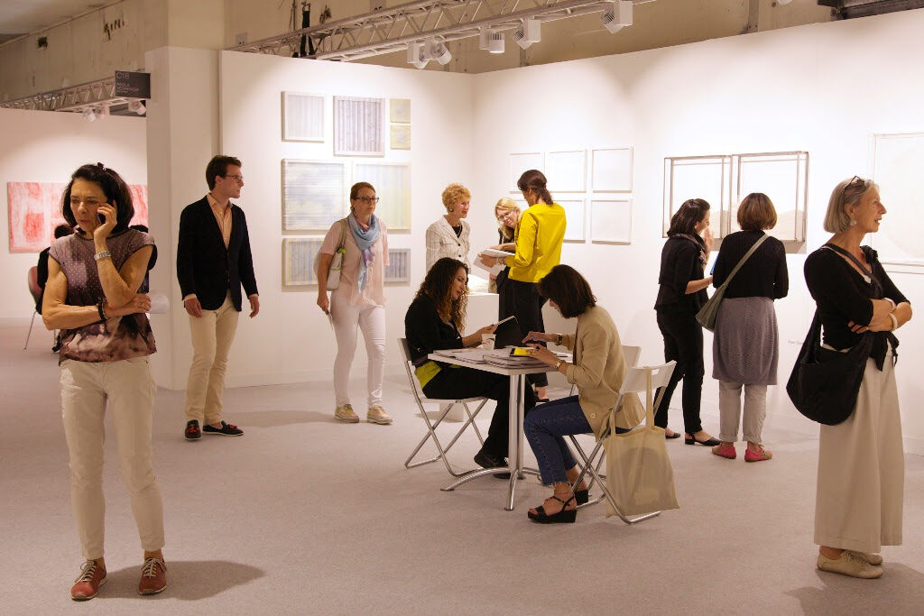 At Galleria Paola Verrengia (Salerno), artist Amparo Sard, center in yellow, discusses her practice with collectors, as other guests engage with her artworks and those by Kaori Miyayama (left wall) and Maria Elisabetta Novello (center wall, right side)