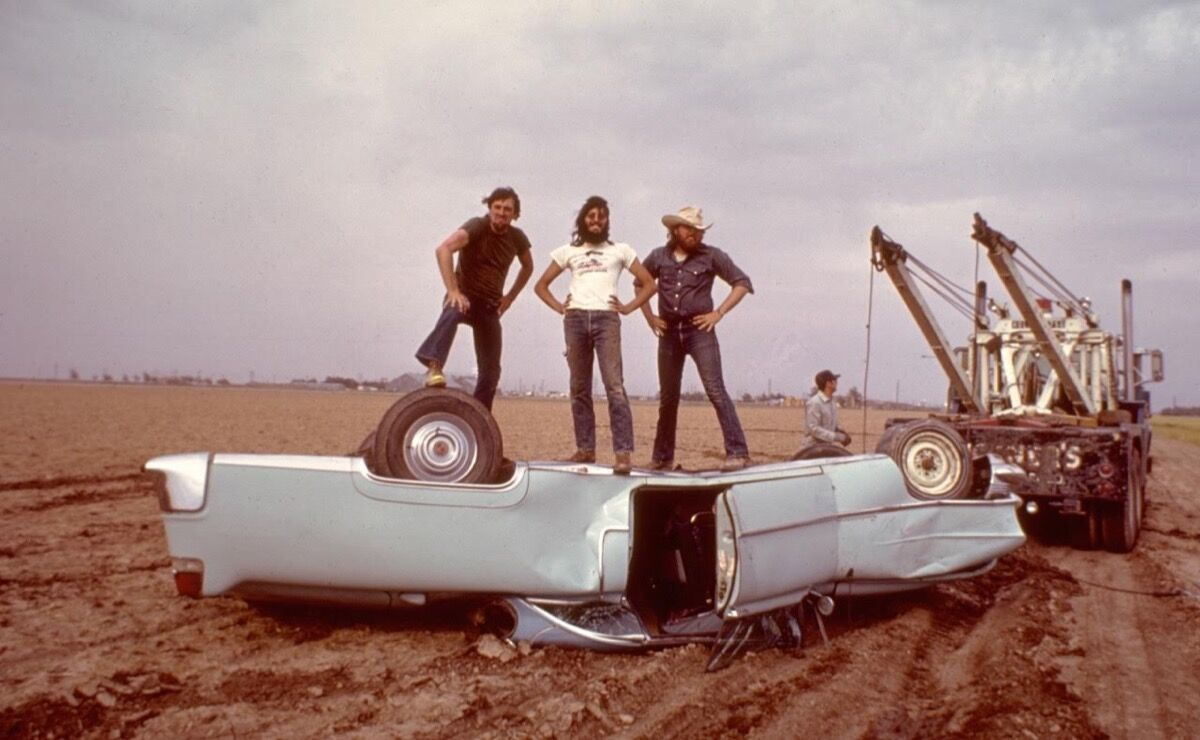 Ant Farm members Doug Michels, Chip Lord, and Hudson Marquez strike a pose on a scrapped car (June 18, 1974). Photo courtesy of Chip Lord.